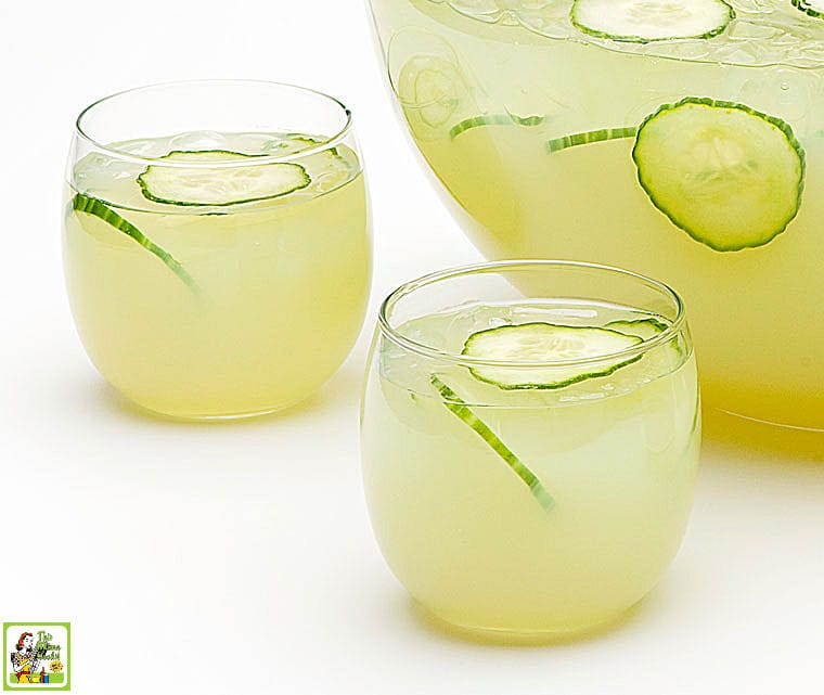 Two cocktail glasses of Sparkling Green Sangria with sliced cucumbers and grapes.