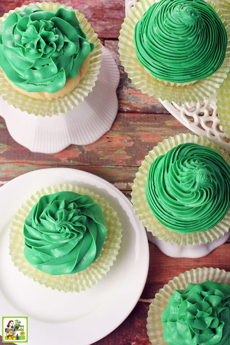 Overhead shot of cupcakes with green frosting with yellow cupcake paper cups on white cake stands.