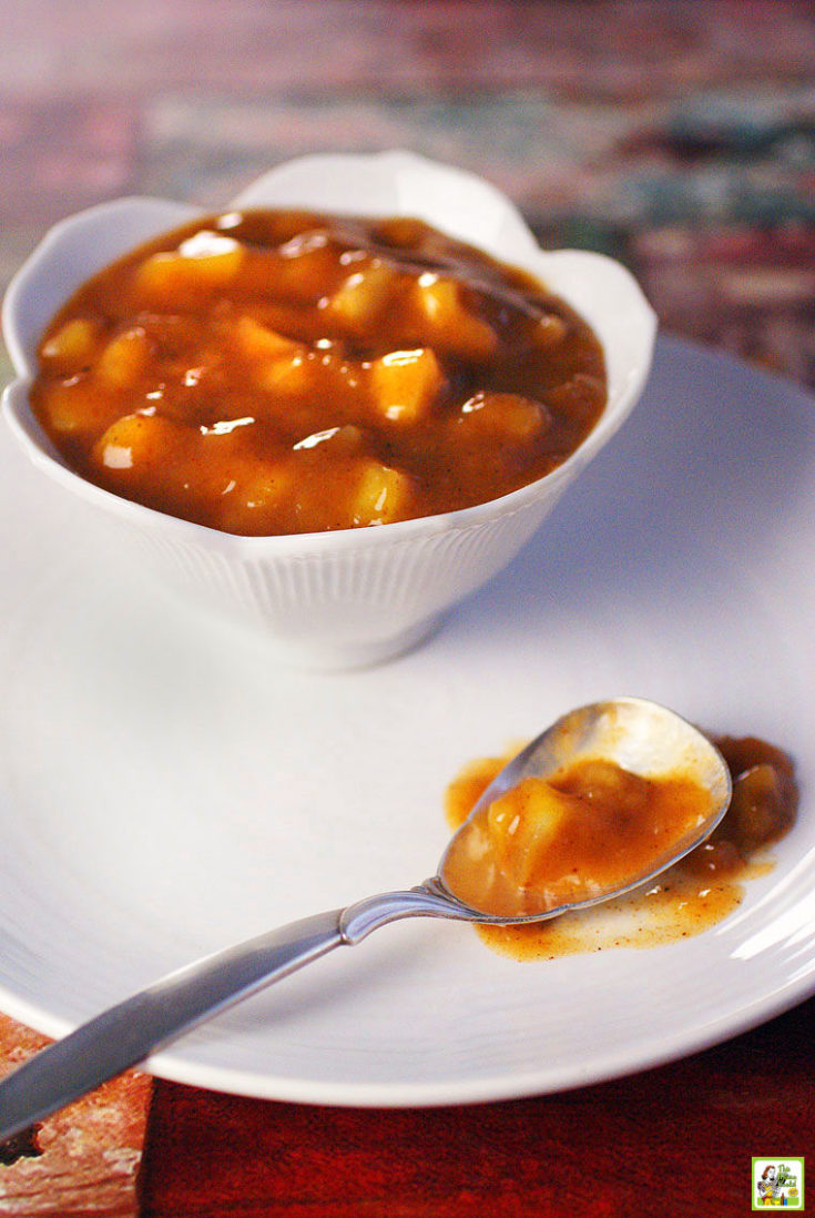 A bowl of healhty apple pie filling with a spoon on a large white plate.