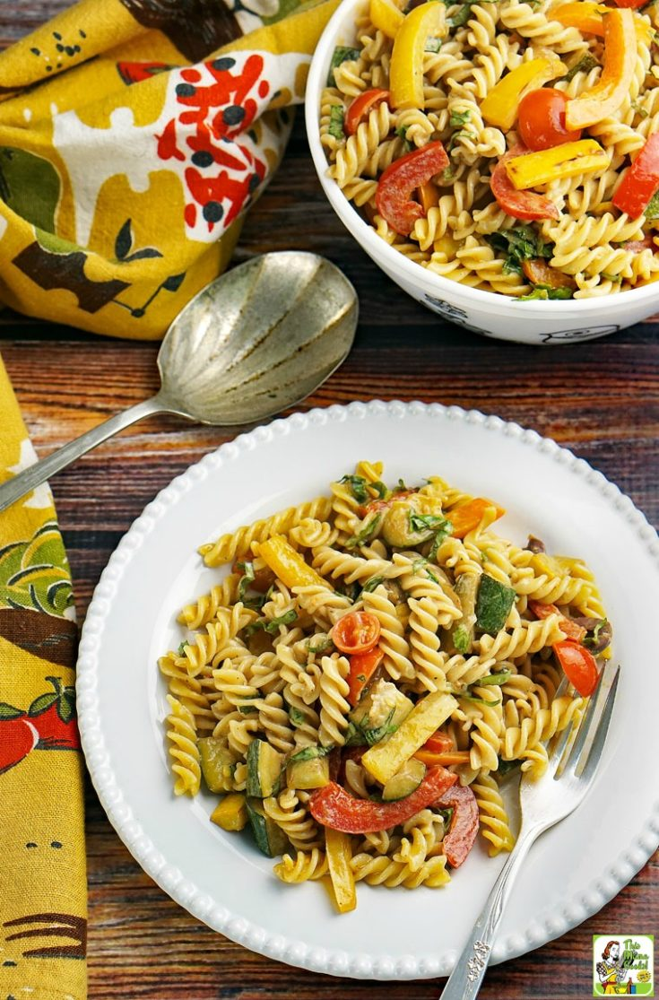 A white plate of pasta salad with roasted vegetables with a bowl of pasta salad, a serving spoon, and napkins.