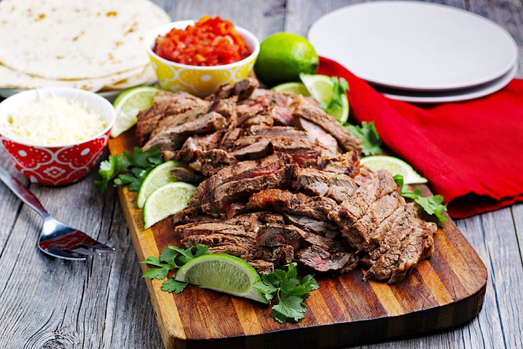 Sliced carne asada meat with limes and cilantro on a wooden cutting board with taco fixings.