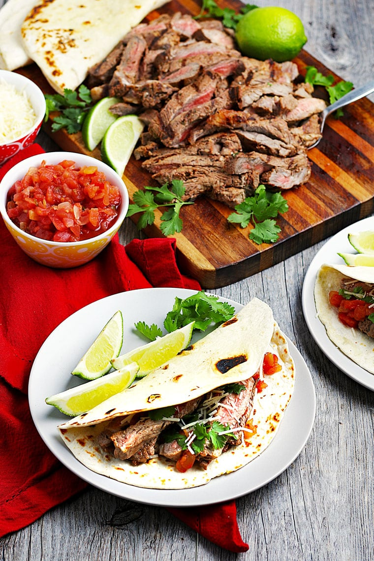 Grilled steak tacos on plates, sliced meat with limes and cilantro on a wooden cutting board, and a bowl of salsa.