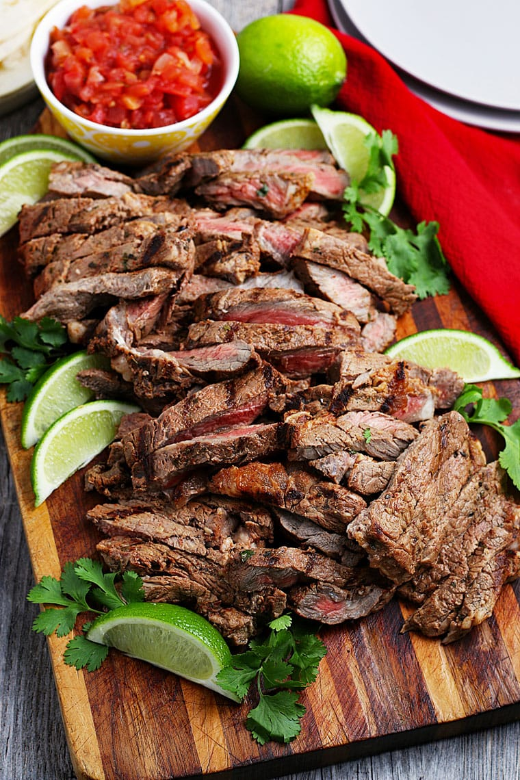 Sliced grilled meat with limes and cilantro on a wooden cutting board and a bowl of salsa.