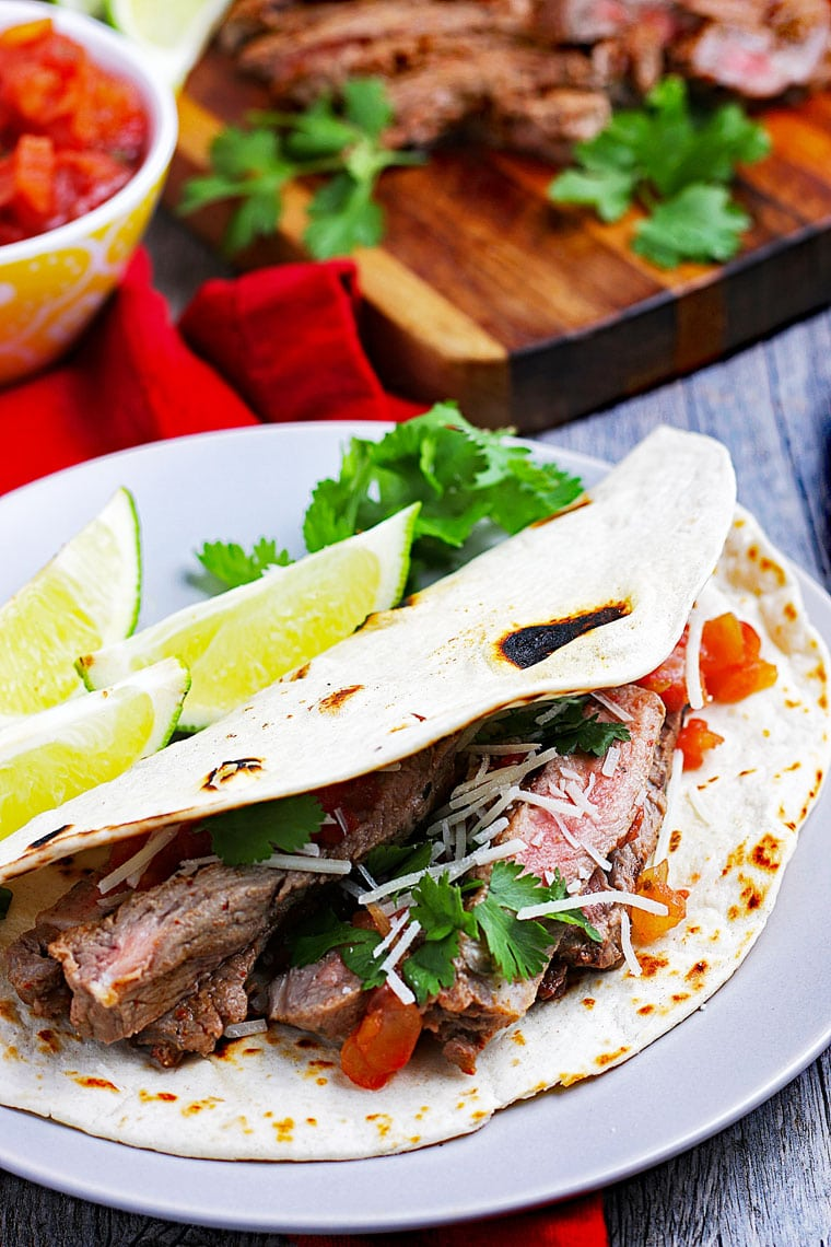 Closeup of a carne asada taco on a white plate with limes with a bowl of salsa and grilled meat on a cutting board.
