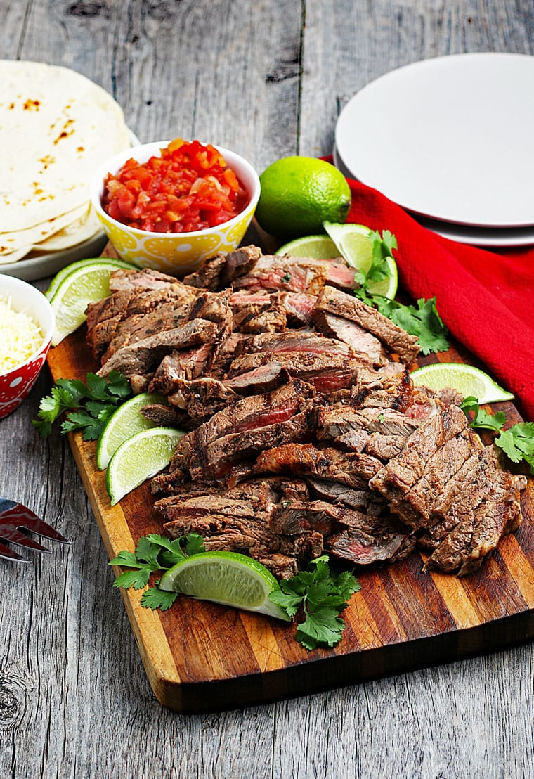 Sliced grilled carne asada meat on a wooden board with a bowl of salsa and slices of lime, white plates, a red napkin, and a pile of flour tortillas.