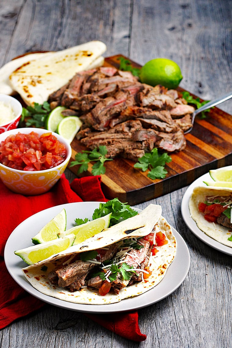 Plates of tacos with sliced meat on a cutting board with a bowl of salsa and plates of tortillas.