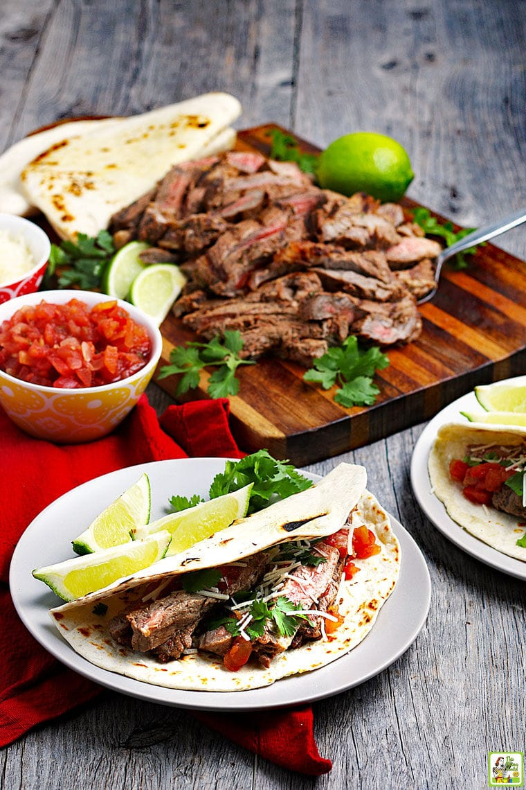 Carne asada tacos and carne asada meat on a wooden board with salsa.