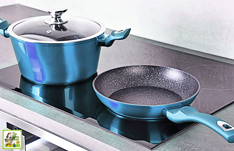 Blue non-stick pot and pan on an induction cooktop stove.