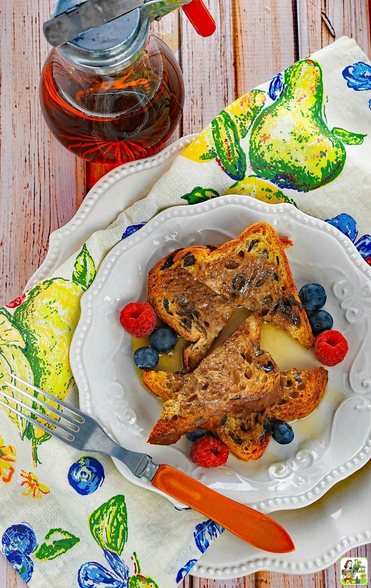 A white plate of French Toast with berries and fork on a colorful napkin with a pitcher of maple syrup
