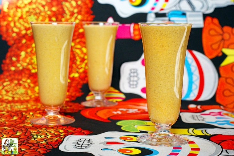Three tall glasses of pumpkin smoothie shakes on Day of the Dead tablecloth