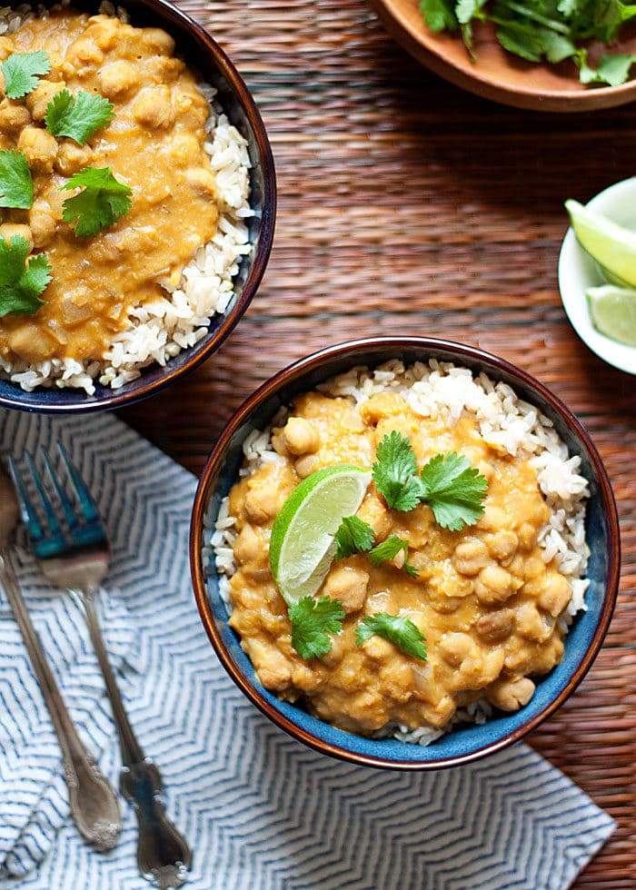 healthy pumpkin recipes: bowls of Slow Cooker Pumpkin, Chickpea, & Red Lentil Curry served on rice with lime