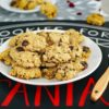 A white plate of gluten free oatmeal cookies with chocolate chips and dried cranberries
