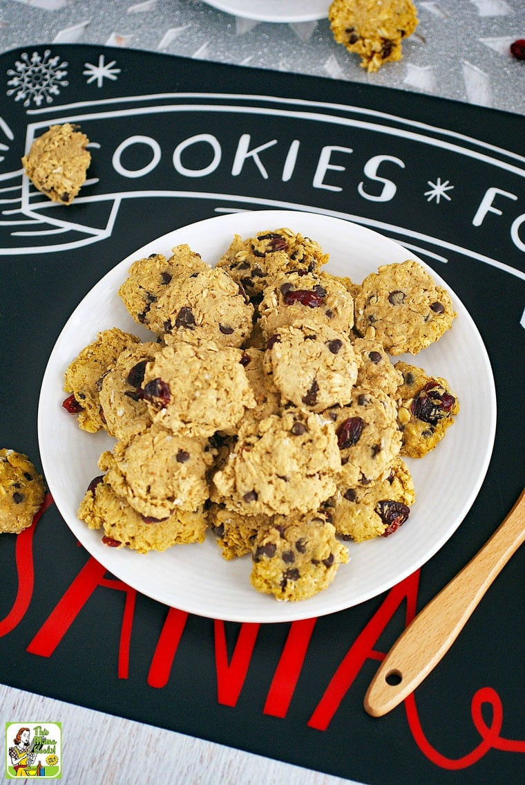Cookies for Santa placemat with a plate of gluten free oatmeal cookies with chocolate chips and raisins, a glass of milk with a straw, and a Santa spatula