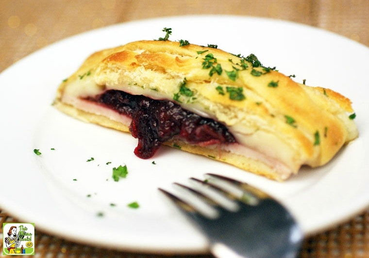 A slice of turkey cranberry crescent braid served on a white plate with a silver fork.