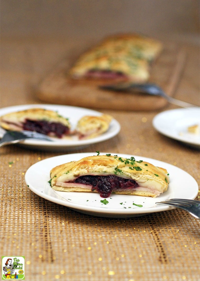 Slices of crescent braid with turkey and cranberry appetizers served on white plates.