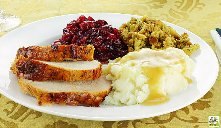 Thanksgiving turkey dinner with mashed potatoes and gravy, stuffing, and homemade cranberry sauce.