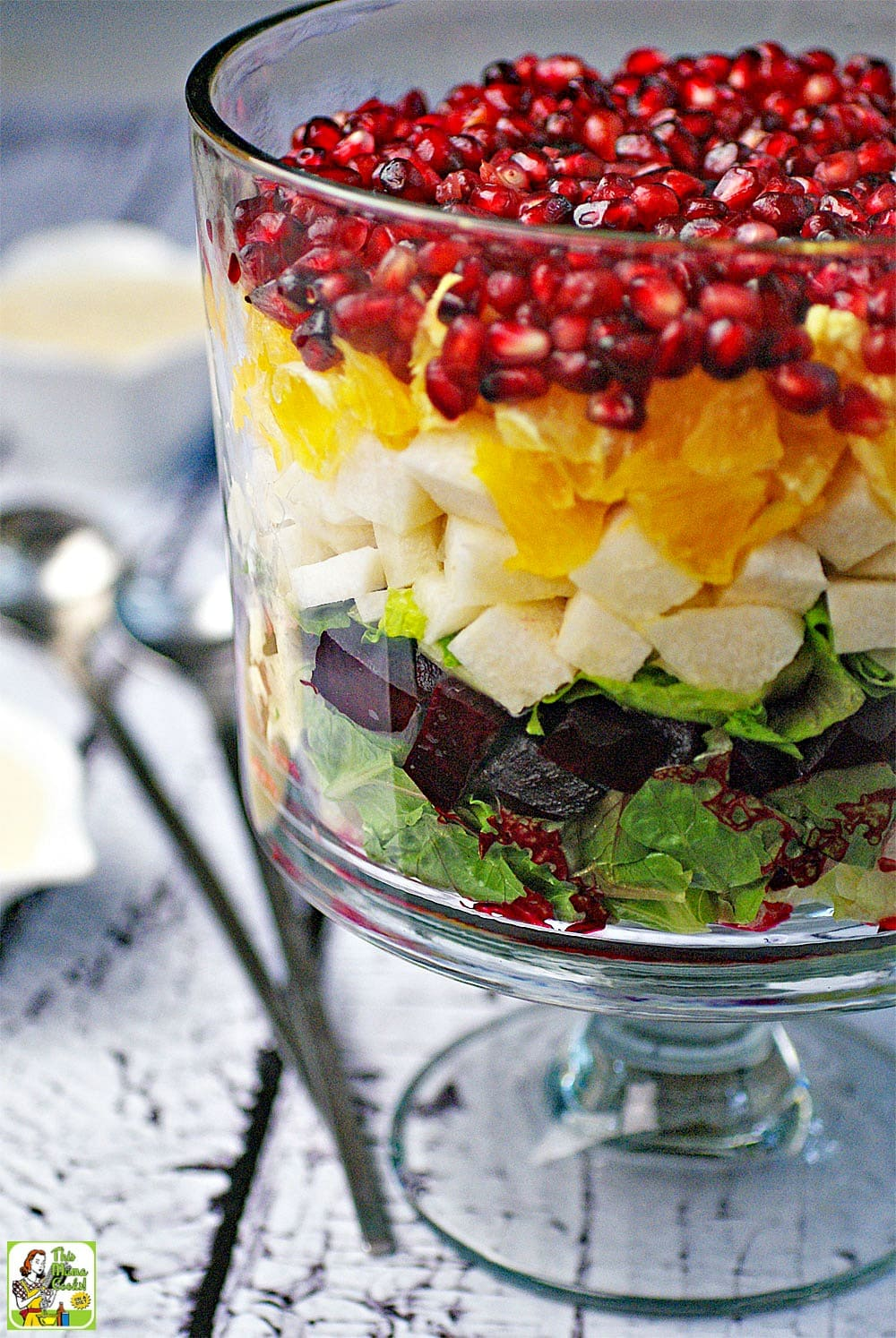 Closeup of a Mexican Christmas Eve Salad in a glass bowl with layers of lettuce, beets, jicama, oranges, and pomegranate seeds.