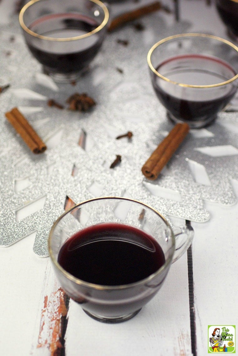 Glasses of slow cooker smoking bishop port wine cocktail and cinnamon sticks.