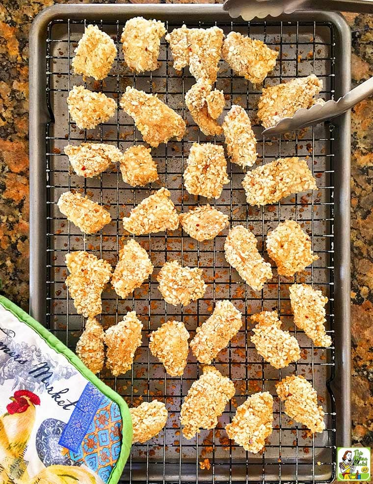 A baking tray of Homemade Chicken Nuggets with pot holder.