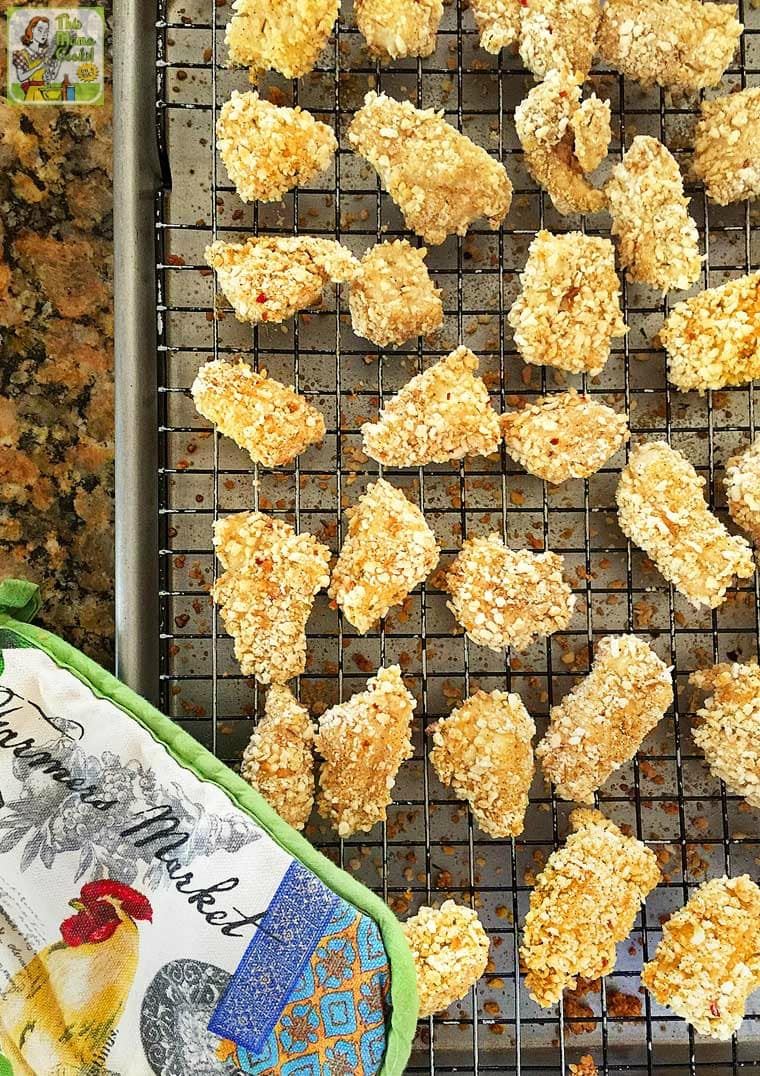 A baking tray of Chicken Nuggets with oven mitt.