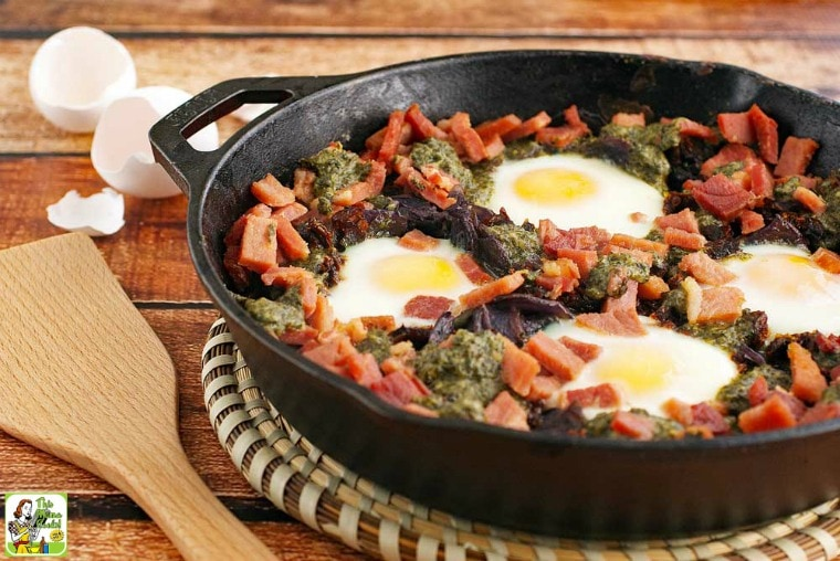 Baked eggs, ham, potatoes, sun dried tomatoes, and pesto in a skillet with a wooden serving spoon.