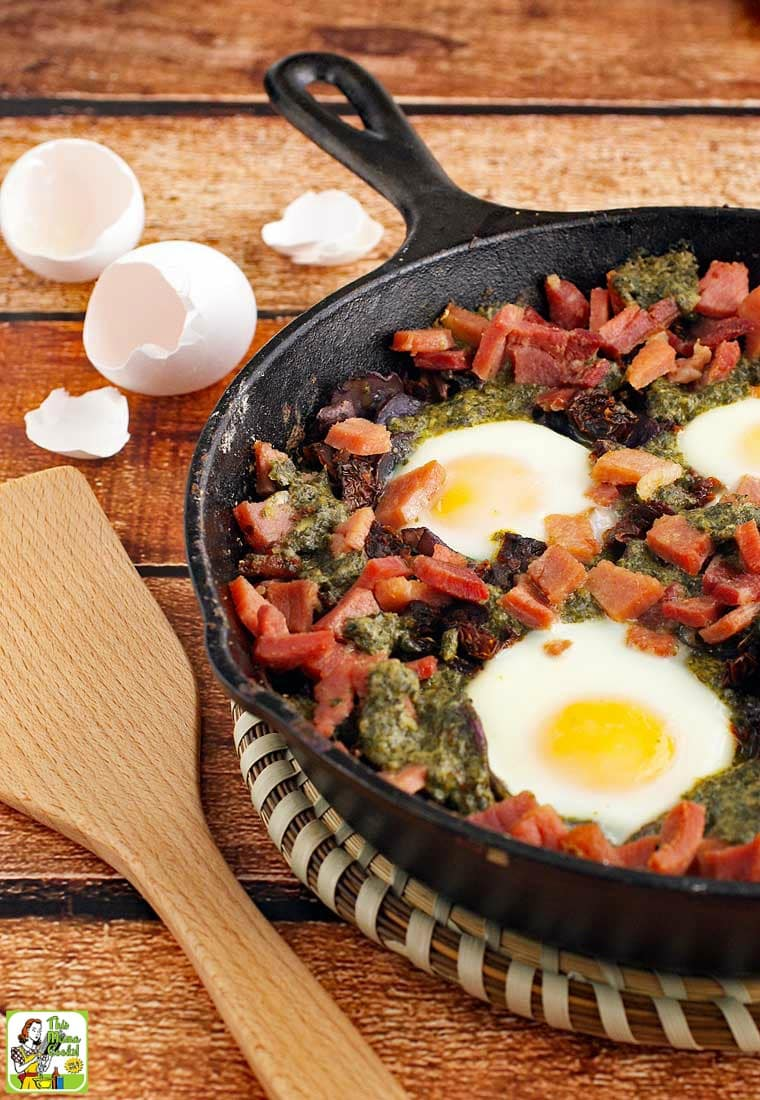 Baked eggs, ham, potatoes, and pesto in a skillet with a wooden spatula.