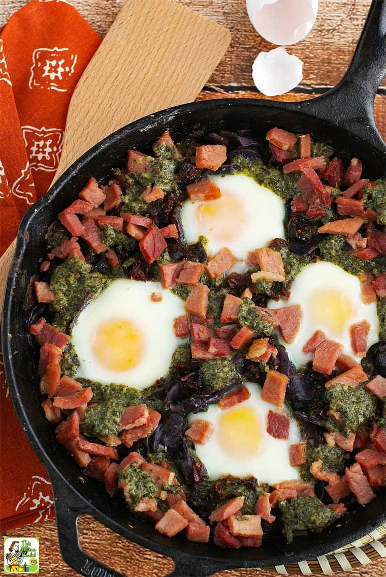 Overhead shot of baked eggs, ham, sun dried tomatoes, potatoes, and pesto in a cast iron skillet.