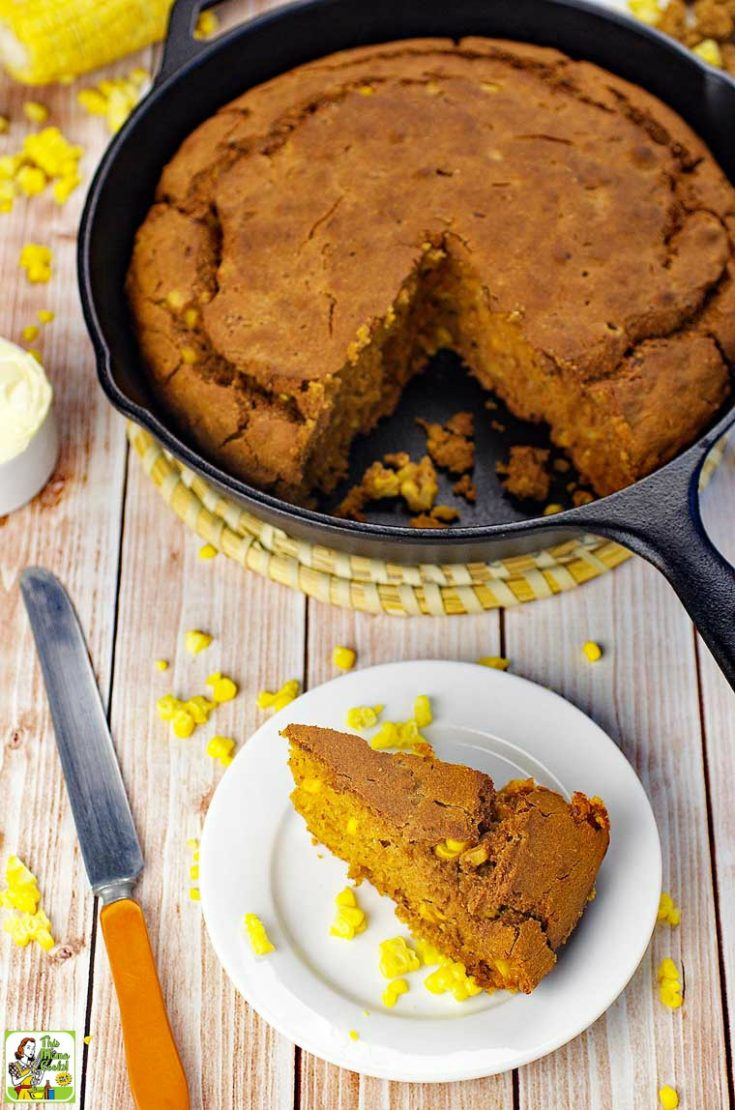 A skillet of cornbread, a slice of cornbread on a white plate, a knife, and kernels of corn.
