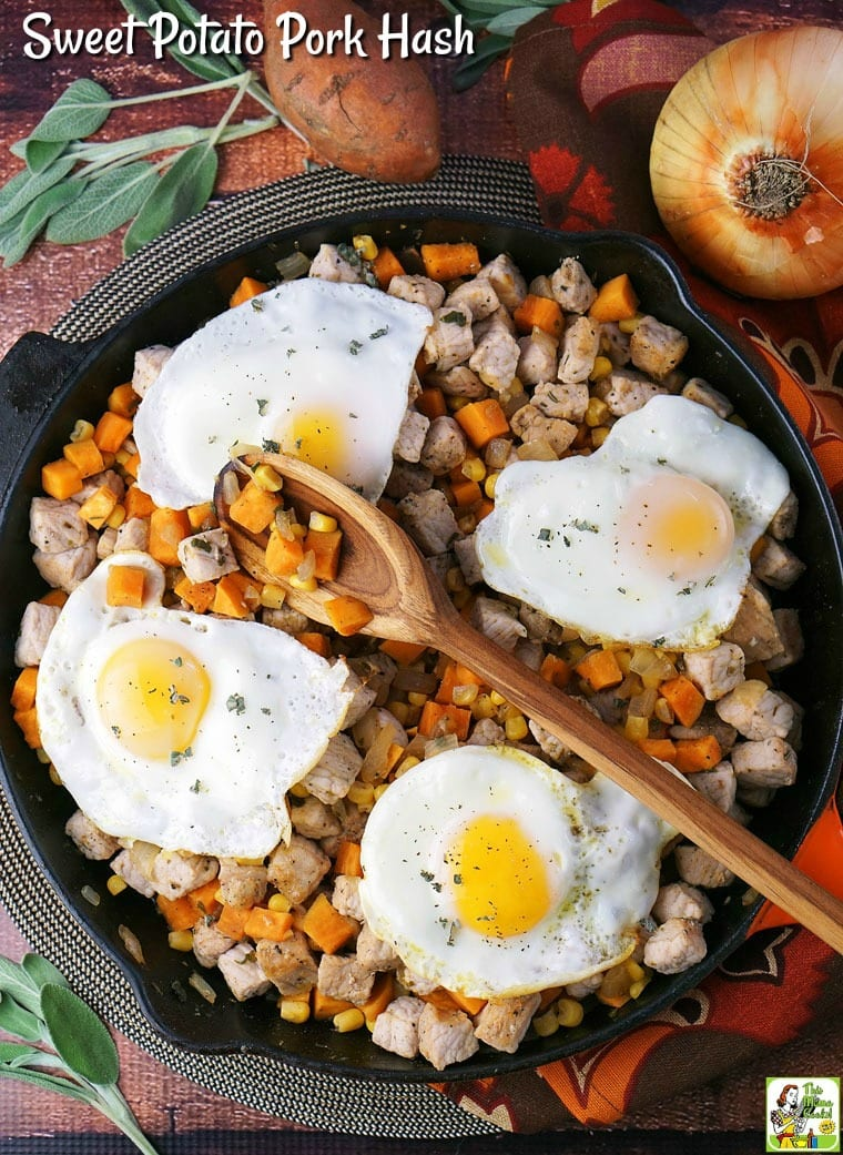 A cast iron skillet of Sweet Potato Pork Hash, sunny side up eggs, and a wooden spoon, surrounded by ingredients - onion, sweet potato and sage