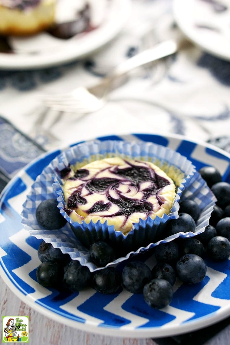 A small blue plate with mini cheesecake and blueberries.