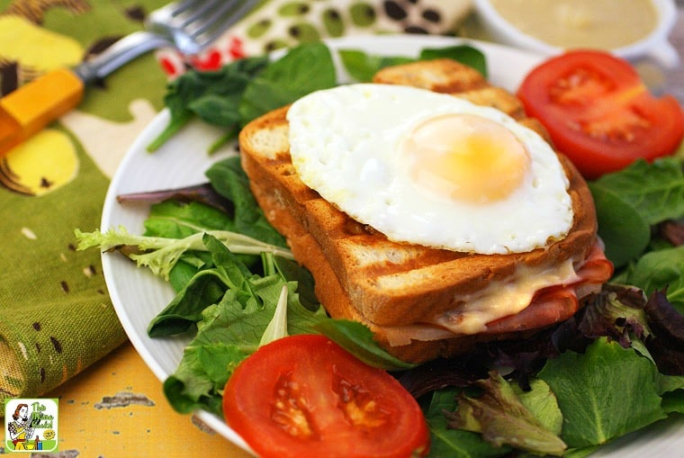 A plate with lettuce, a grilled ham and cheese Croque Monsieur sandwich with an egg, and sliced tomatoes