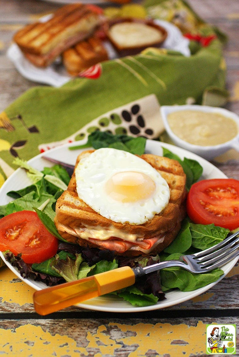 A plate with lettuce, a grilled Croque Monsieur sandwich with an egg, a bowl of bechamel sauce, and sliced tomatoes.