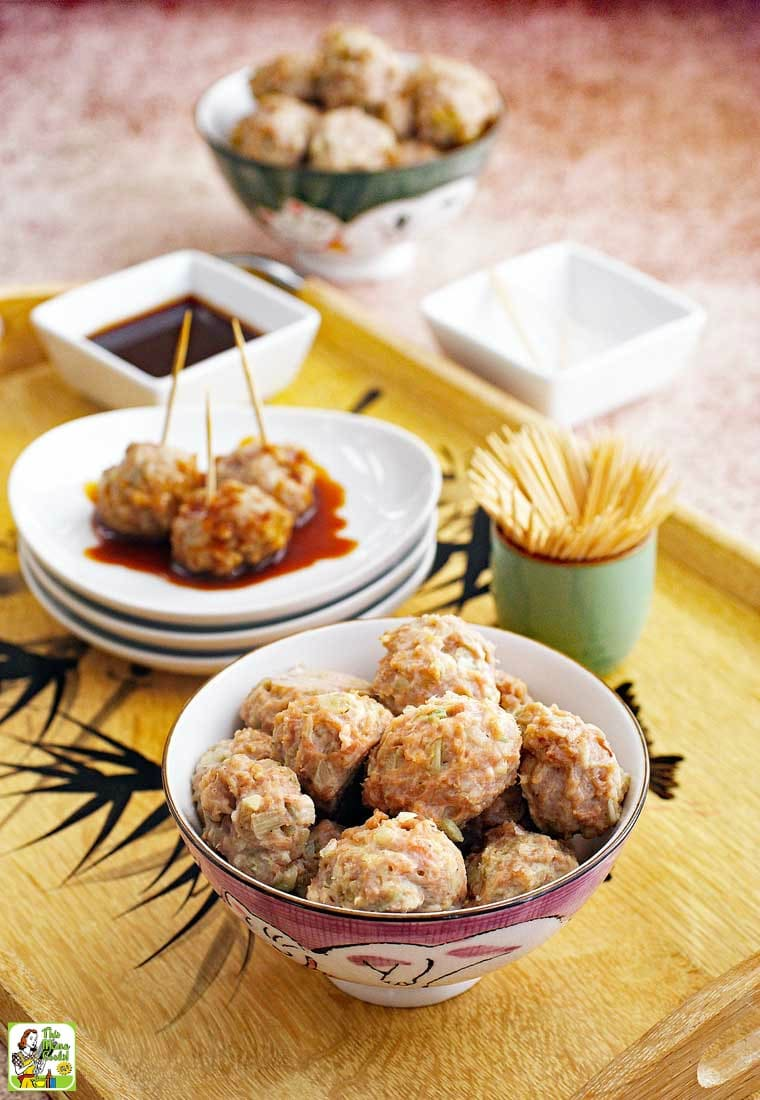 A tray of Asian style pork meatball appetizers with a bowl of dipping sauce.