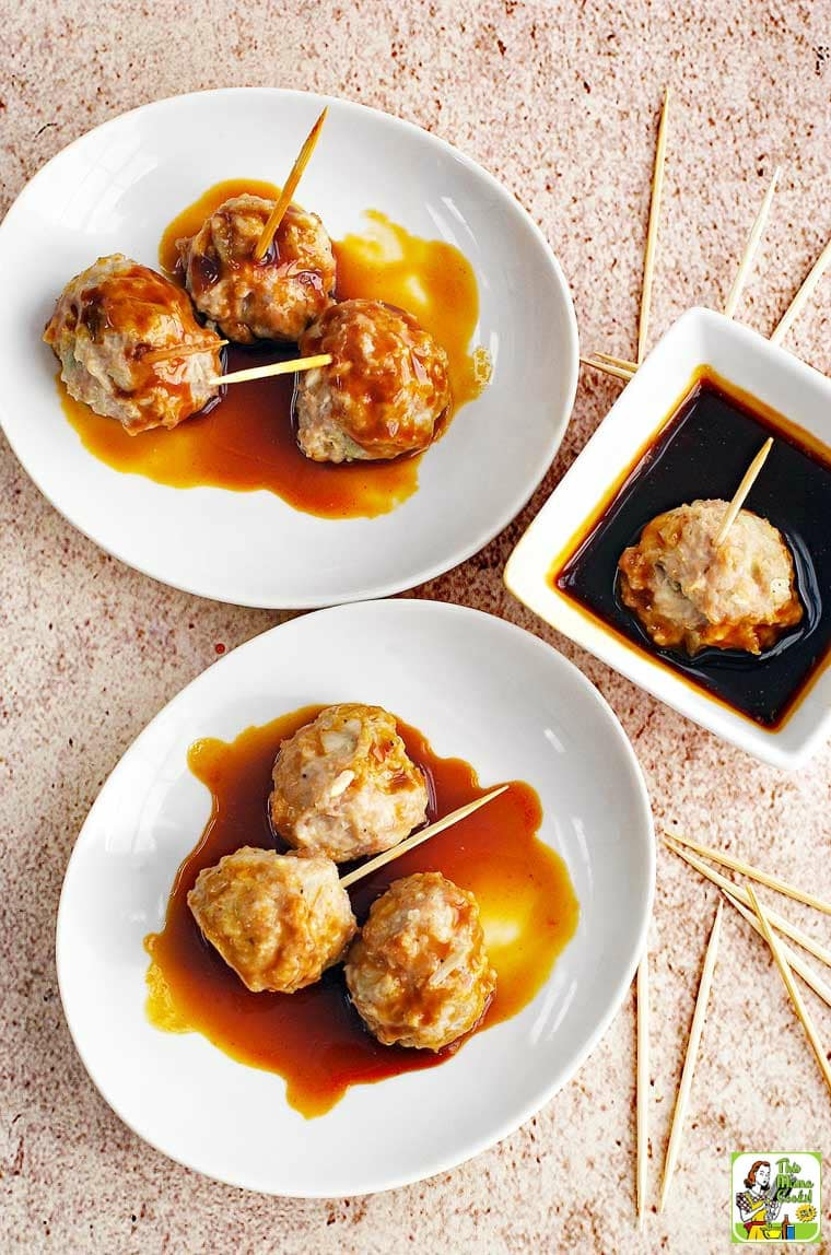 A bowl and plate of Asian style pork meatball appetizers served on toothpicks with a small bowl of dipping sauce. With extra toothpicks.