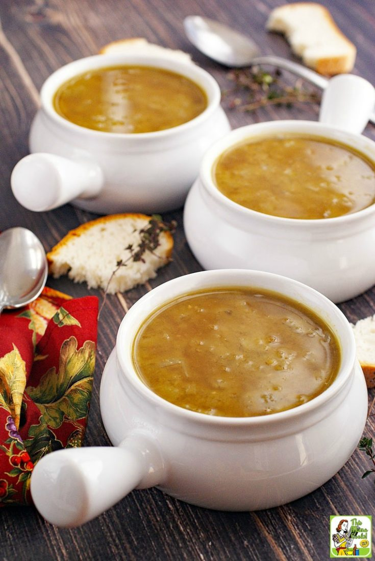 Three bowls of split pea soup with bread, sprigs of thyme, spoons, and red napkins.