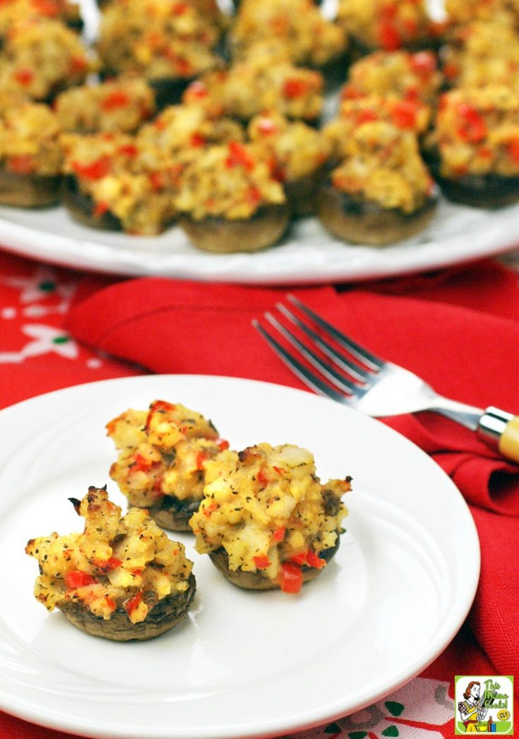 Several stuffed mushrooms on a white plates with fork.