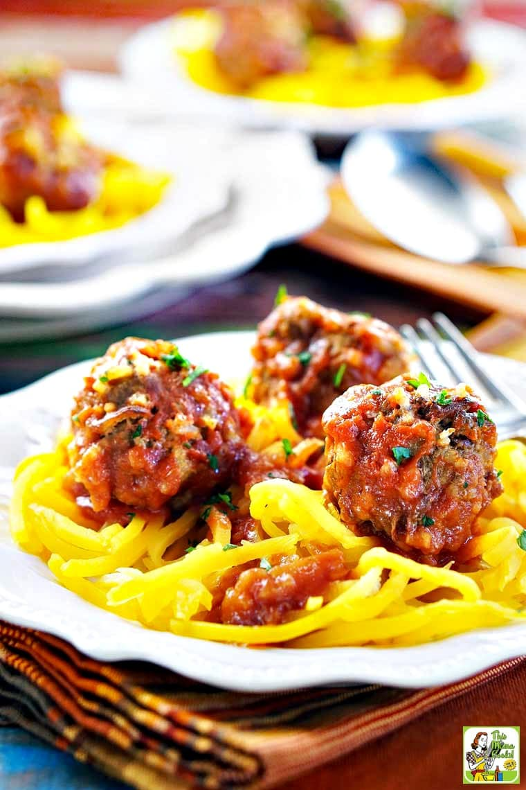 Closeup of a white plate of Slow Cooker Porcupine Meatballs served on butternut squash zoodles