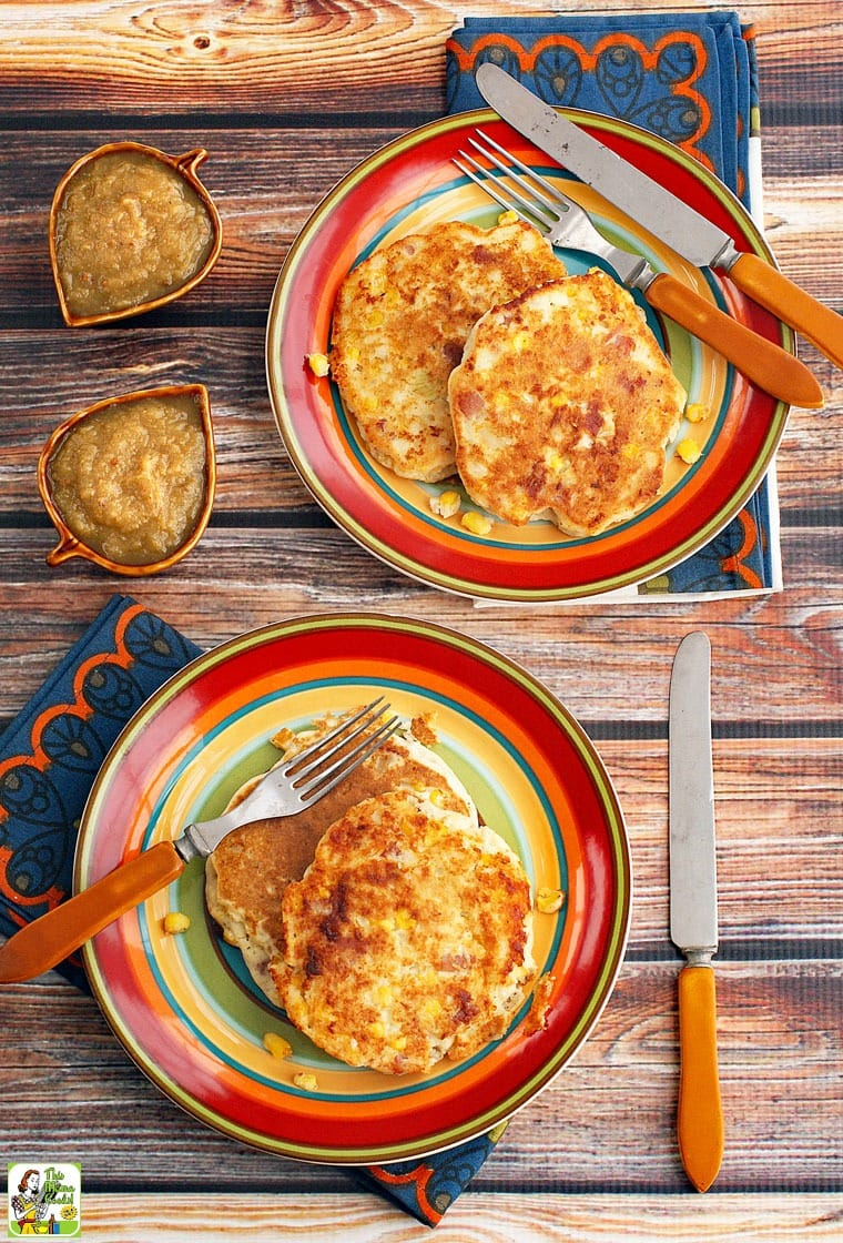 Corn Fritters on a striped plates with a forks, knives and napkins and bowls of apple sauce.