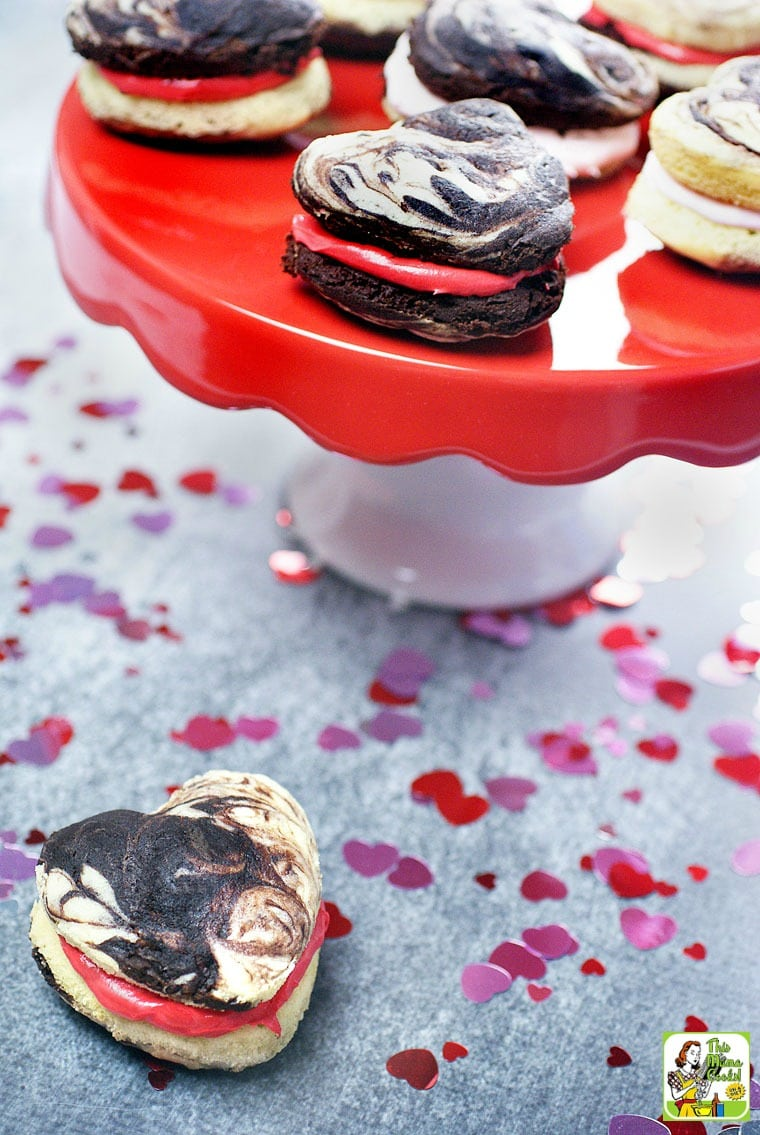 Heart shaped whoopie pies with red and pin filing on a red and white cake stand.