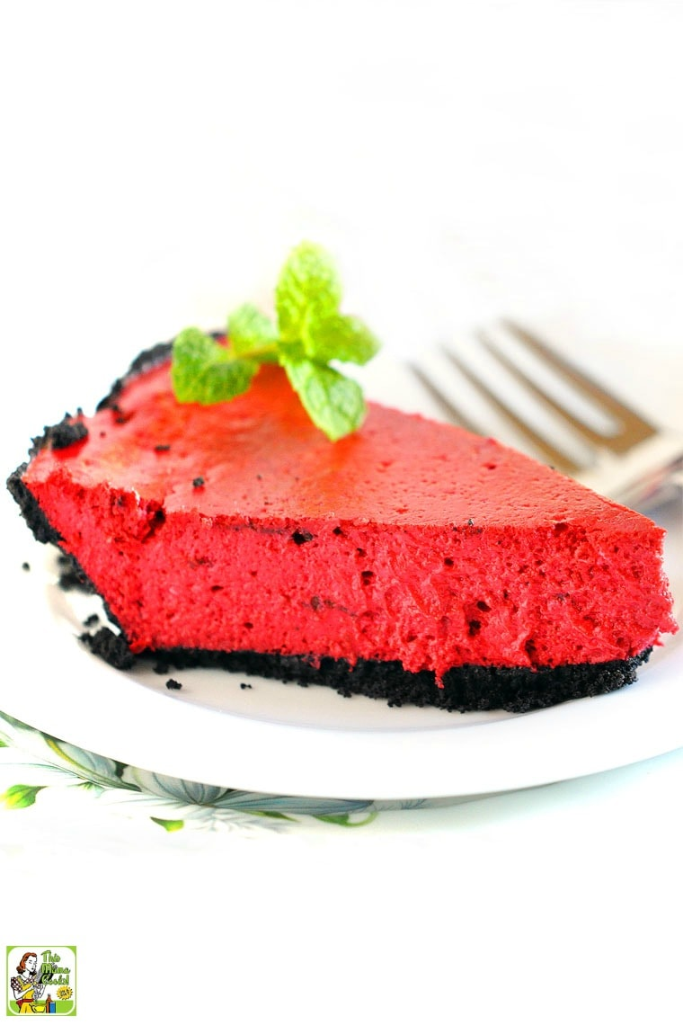 A slice of Red Velvet Cheesecake with a chocolate crust on a white plate. Garnished with a sprig of mint.