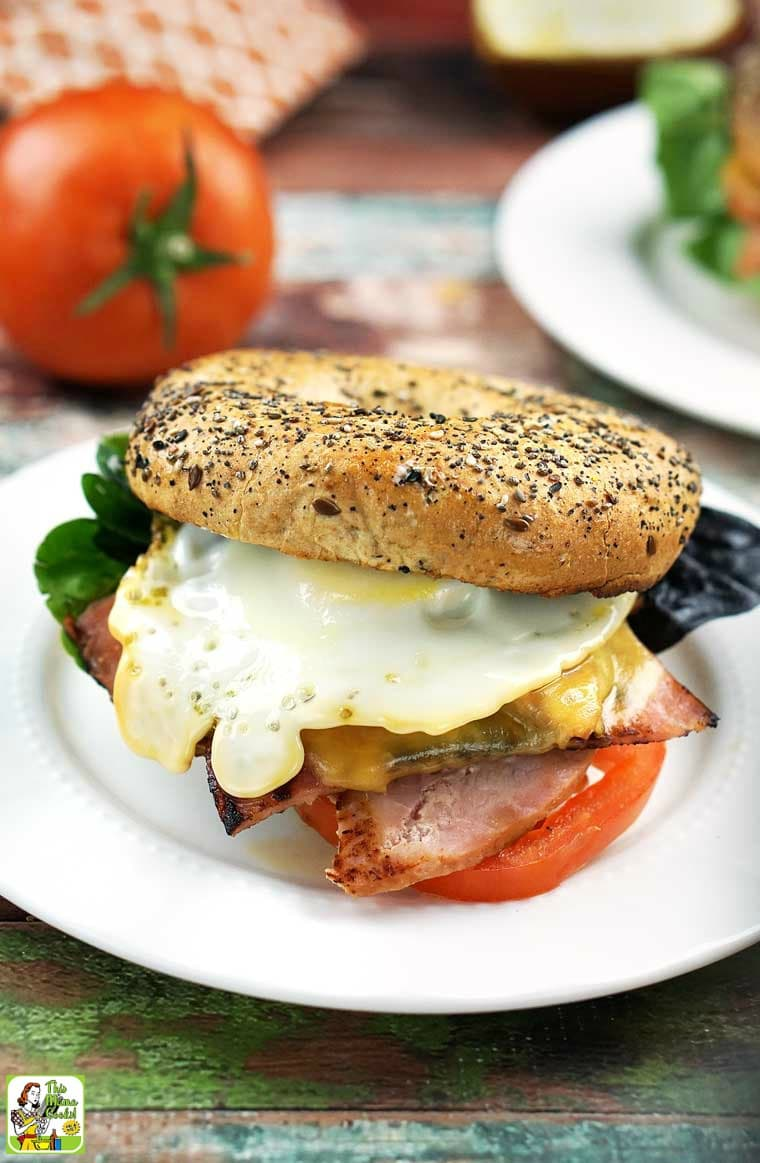 An egg, ham and cheese bagel sandwich on a white plate.