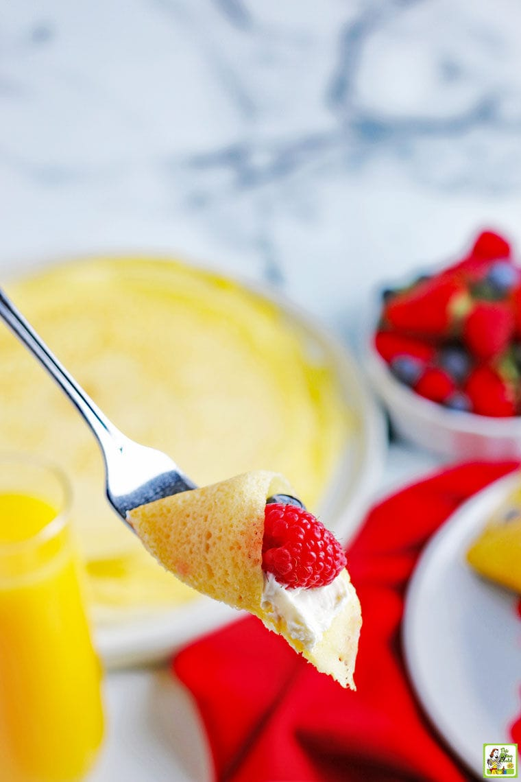 A forkful of cream and raspberry filled gluten free crepe with berries and crepes in the background.