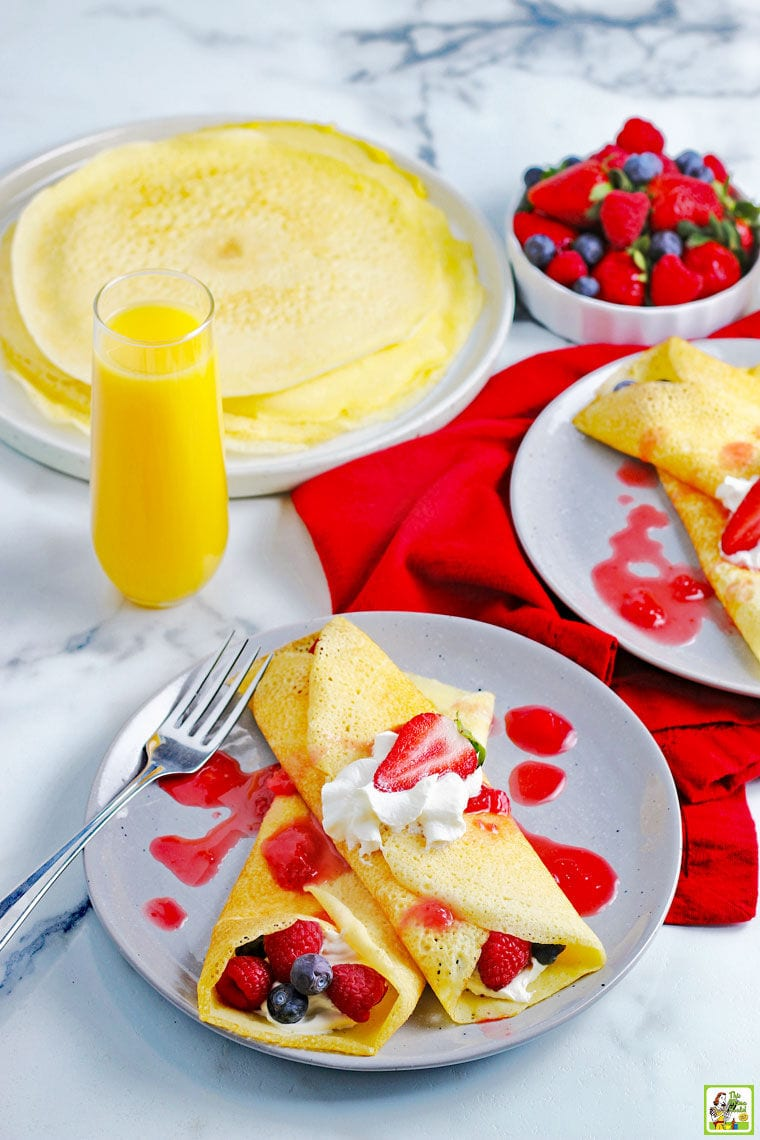 A tabletop with plates of gluten free crepes with berries, whipped cream, a glass of orange juice, and a bowl of raspberries and blueberries.
