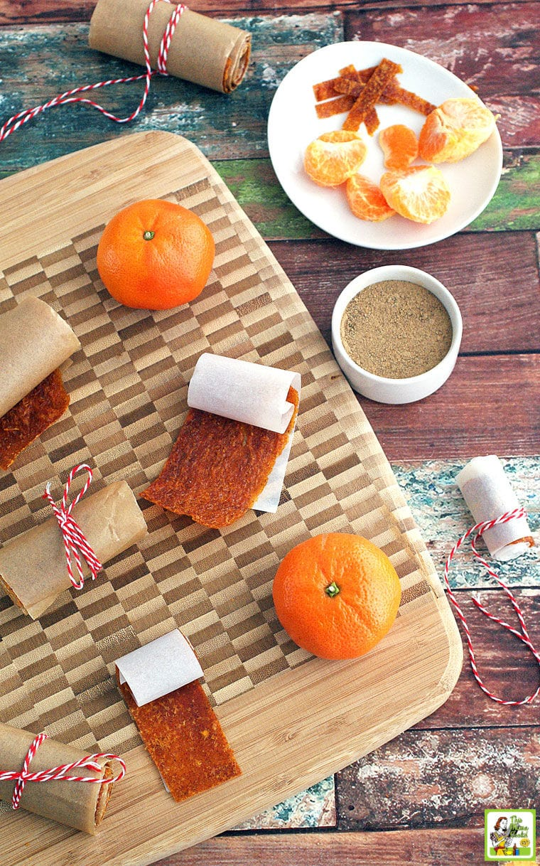 Orange Fruit Leather rollups, oranges, and spices on a wooden cutting board.