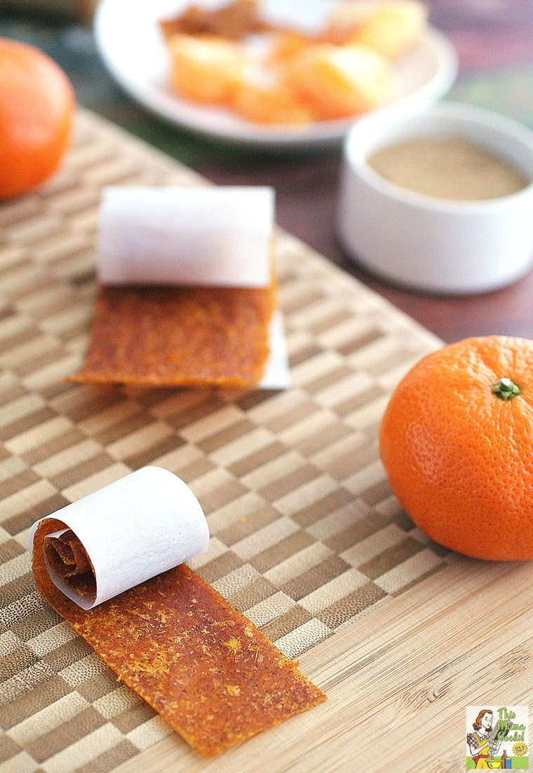 Closeup of Orange Fruit Leather rollups and oranges on a wooden cutting board with spices and orange slices in the background.
