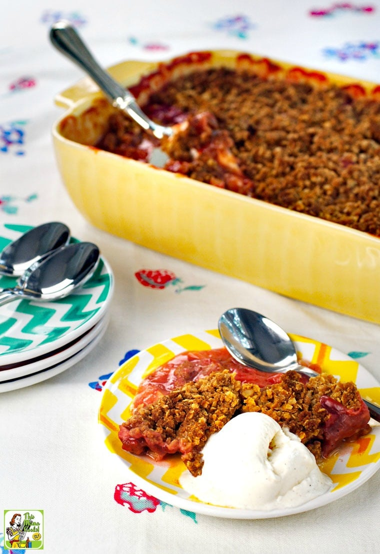 A small  plate of rhubarb crisp and a scoop of vanilla ice cream and a large casserole dish rhubarb crisp with more plates and spoons.
