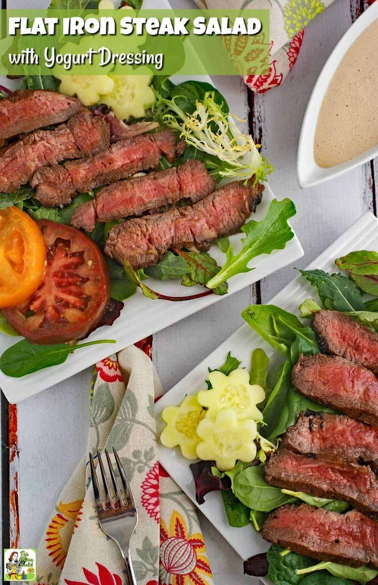 Closeup of plates of Flat Iron Steak Salad with Yogurt Dressing with salad and tomatoes with fork, napkin, and pitcher of dressing.