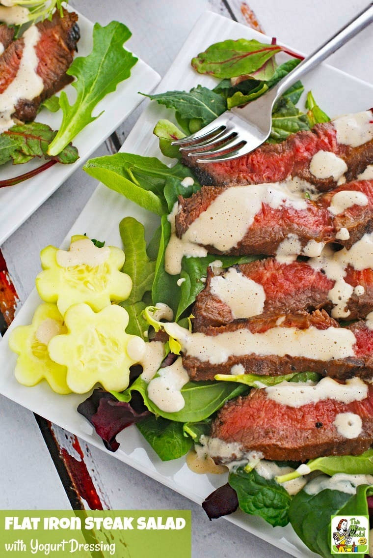 Closeup of a plate of Flat Iron Steak Salad with Yogurt Dressing with salad and tomatoes.