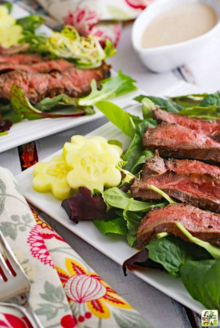 Closeup of Flat Iron Steak Salad with Yogurt Dressing with napkin and fork.