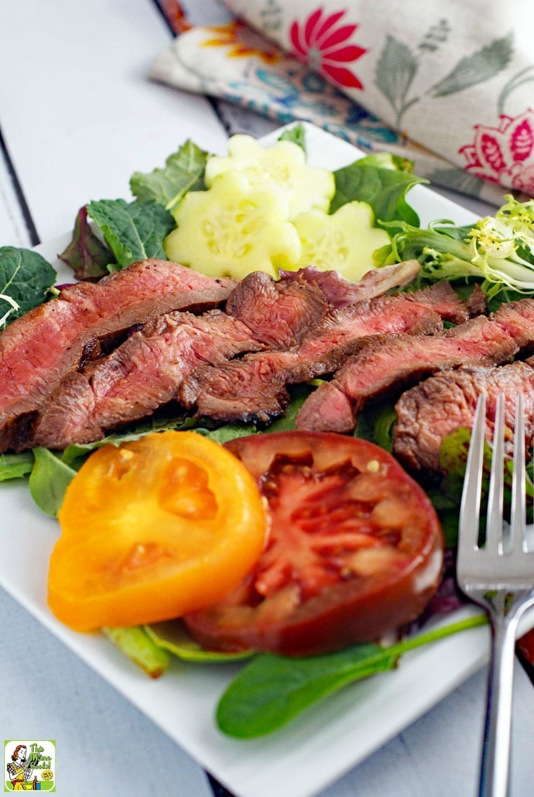 Closeup of Flat Iron Steak Salad with Yogurt Dressing with sliced tomatoes and fork.